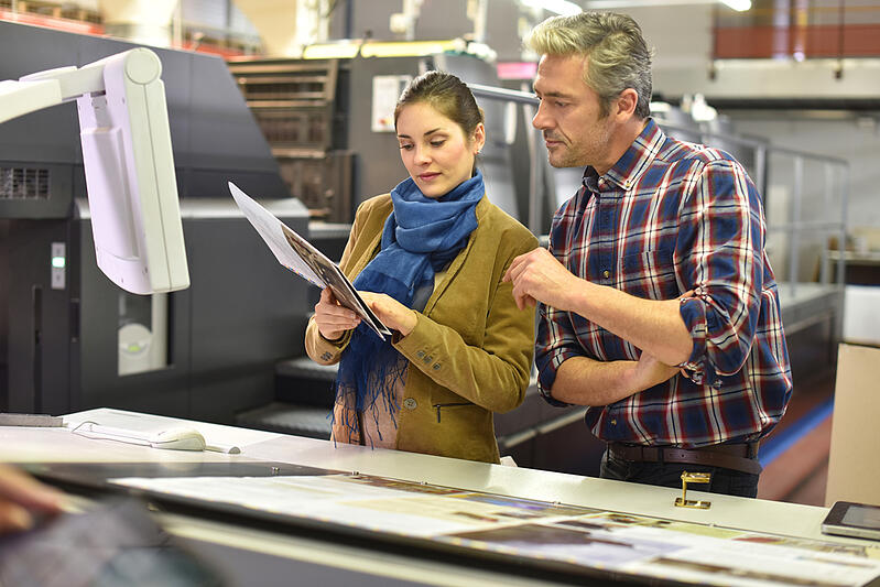 Man in printing house showing client printed documents